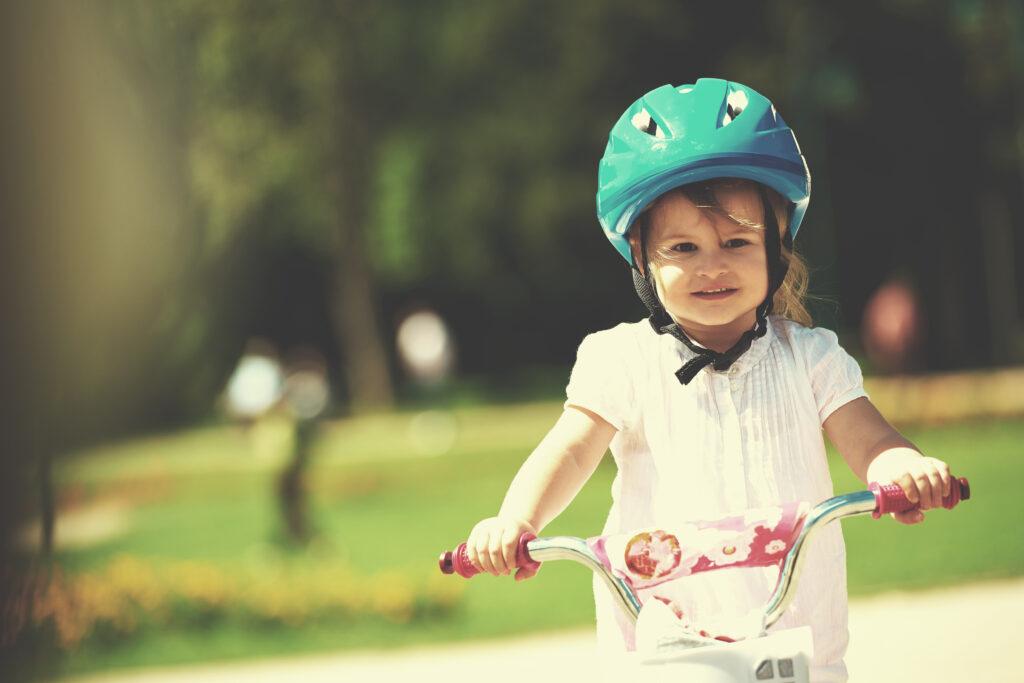 dziewczynka w kasku jedzie na rowerze